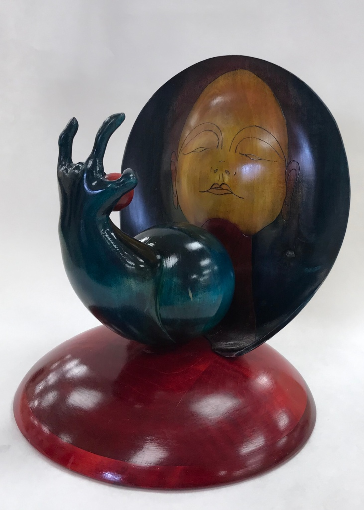 Turned and carved sculpture in wood depicting a sublime face of Virgo  as she is offered the strawberry moon by Mother Earth