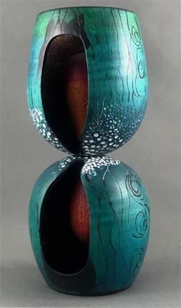 two wood-turned wine glass forms joined at their base to create a waited form. an hour-glass shape is carved out and inside we see the timer counting down. The outside is embellished with representations of polar ice, sea currents and wind